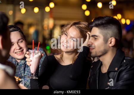 Gli amici sorseggiando un caffè insieme. per uomo e donna presso il cafe, parlare, ridere Foto Stock