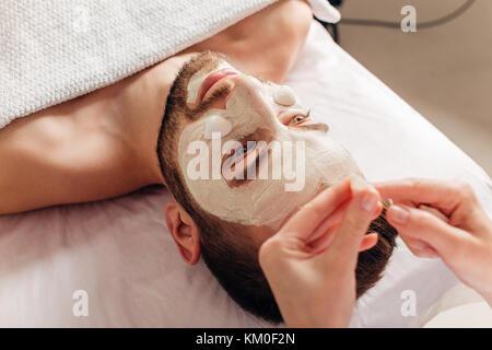 L uomo nella maschera di procedura di cosmetici in spa salone Foto Stock