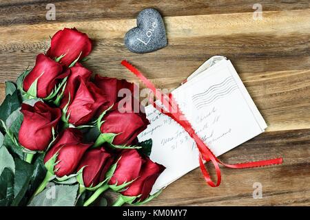 Gambo lungo rose rosse con una pila di vecchi lettere legate con un nastro rosso e carta un po' di cuore di pietra con la parola amore. Foto Stock