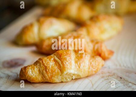 Black croissant con caffè nero su sfondo di legno Foto Stock