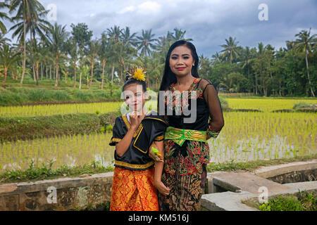 Giovane donna e bambina in splendidi costumi tradizionali in campi di riso vicino tetebatu sull'isola di Bali, Indonesia Foto Stock