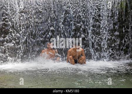 Due ragazzi indonesiano la balneazione in benang kelambu cascate sulle pendici del vulcano rinjani, central lombok, Foto Stock