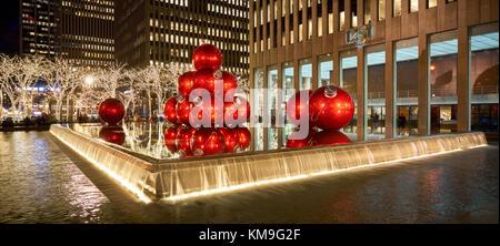 Rossa gigante ornamenti di Natale sulla 6th Avenue con la stagione delle feste decorazioni. Avenue of the Americas, Midtown Manhattan, a New York City Foto Stock