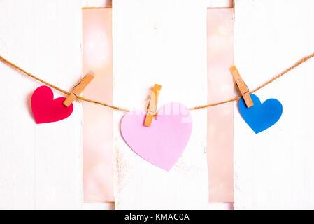 Il giorno di san valentino immagine con un grande cuore rosa al centro, uno rosso e uno blu sui lati, costituito da carta e legato a una stringa con clip in legno Foto Stock