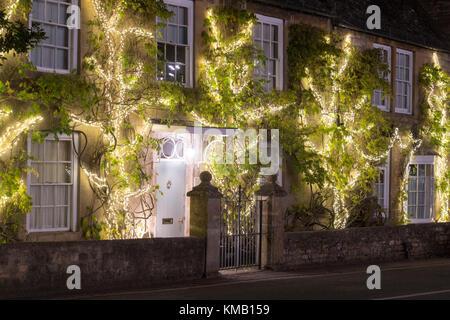 Luce di Natale decorazioni sulla facciata di una casa in piante di glicine in Broadway di notte. Broadway, Cotswolds, Worcestershire, Inghilterra