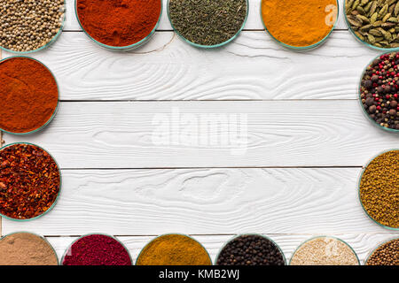 Le spezie in ciotole in vetro sul tavolo bianco Foto Stock