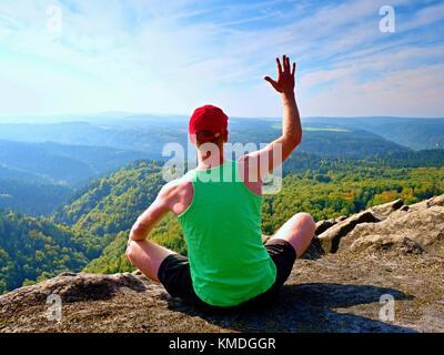 Sottile corpo escursionista in verde canotta e pantaloncini neri a sedersi su una roccia e godere di scenari naturali. Foto Stock