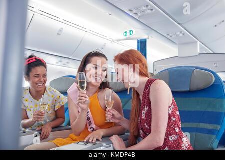 Giovani donne amici ridere,bevendo champagne in prima classe in aereo Foto Stock