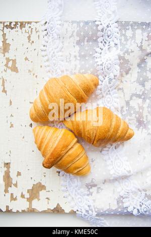 Bella e deliziosi croissant sullo sfondo di vecchi pizzi e tavolo bianco Foto Stock