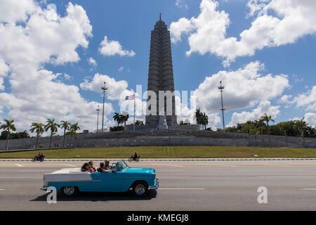I turisti prendere un classico giro in macchina per la plaza de la Revolución a l'Avana, Cuba. Foto Stock