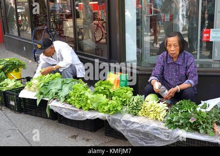 Un anziano uomo asiatico e la donna la vendita di verdure fresche sul marciapiede di Toronto chinatown a Toronto Foto Stock