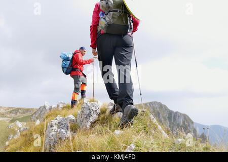 Close-up di gambe di giovani escursionisti a piedi sul percorso del paese. Coppia giovane trail veglia. Focus su Foto Stock