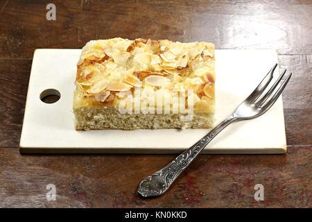 Tradizionale Tedesco del Nord Butterkuchen (burro torta) sul vecchio tagliere. Foto Stock