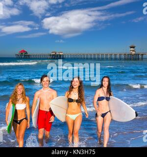 Ragazzi e ragazze teen surfers uscente dal morbo di Huntington Beach in California. Foto Stock