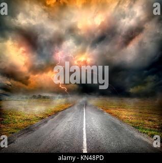 Nuvole di tempesta e fulmini su autostrada nel campo. Foto Stock