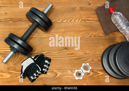 Concetto per esercizio fisico e lo sport. Il manubrio, guanti, asciugamani, acqua su un sfondo di legno Foto Stock