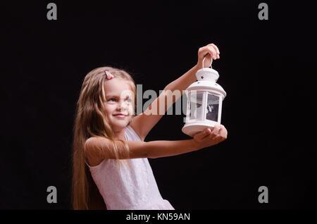 Bambina di cinque anni in piedi con un candelabro. Foto Stock