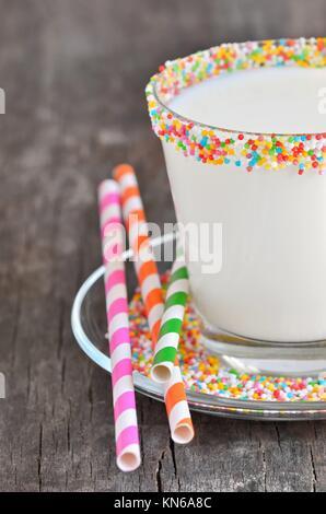 Un bicchiere di latte con cannucce a strisce. Foto Stock