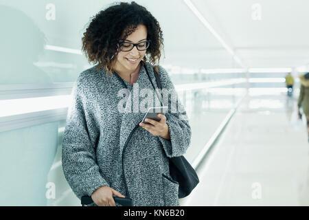 Afro American Girl sms e utilizzando uno smartphone Foto Stock