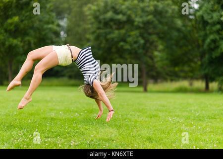 Giovane ragazza sportiva salta indietro al parco, immagine con profondità di campo ridotta. Foto Stock