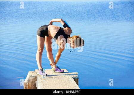 Runner donna stretching in un lago pier all'aperto. Foto Stock