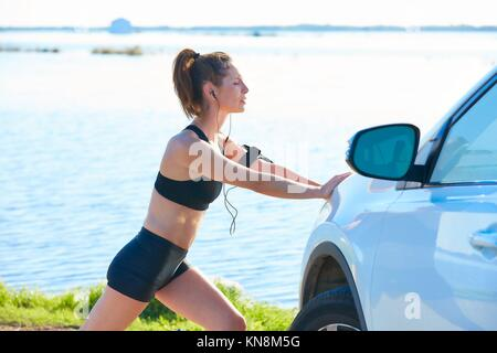Runner donna stretching su una vettura nel lago all'aperto. Foto Stock