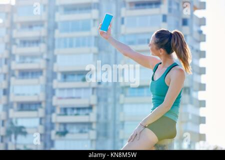 Runner ragazza avente un riposo selfie riprese con lo smartphone edificio esterno park. Foto Stock