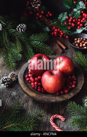 Le mele rosse, mirtilli e Abete rami. Natale ancora in vita. Lo sfondo inverno. Composizione verticale