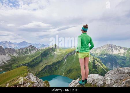 Vista posteriore di un escursionista femmina sul bordo roccioso affacciato su montagne di Tannheim, Tirolo, Austria Foto Stock
