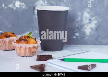 Pausa caffè con tortini di cioccolato, il blocco note e penna, coffee break in studio e la concezione di business. Foto Stock