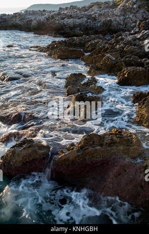 Le onde rompono sulle rocce della costa Kardimyli, costa ovest della Grecia, al tramonto Foto Stock