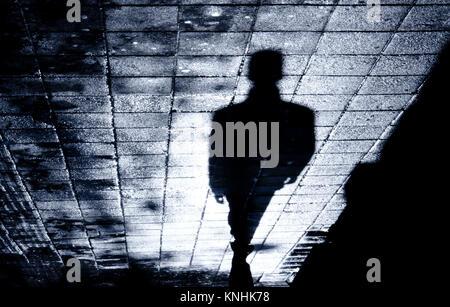 Sfocata l'ombra e la sagoma di un uomo in piedi la notte sulla città bagnata street marciapiede con acqua la riflessione Foto Stock