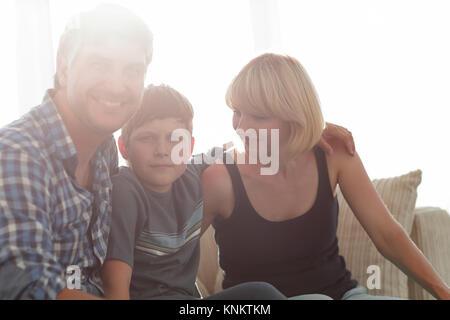 I genitori e il loro figlio sedersi rannicchiato nella stanza vivente e sorridente Foto Stock