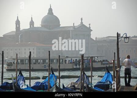 Gondole a un dock in Canal Grande. Davanti la basilica di San Giorgio Maggiore nell'isola di San Giorgio Maggiore. Venezia, Veneto, Italia,