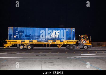 Carrello merci il trasporto di un contenitore blu di merci a Santa Cruz de Tenerife dock di notte Foto Stock