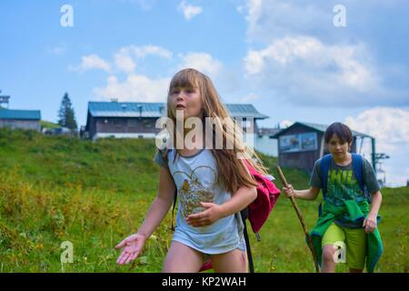 Wanderlust - due bambini godendo di avventura trekking mentre si cammina su verdi pascoli in natura, Brauneck, alpi bavaresi, Germania Foto Stock