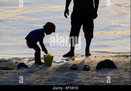 Il padre e il suo piccolo figlio giocando sulla spiaggia al tramonto, Blue Bay beach. Grand Port District, Mauritius, Foto Stock