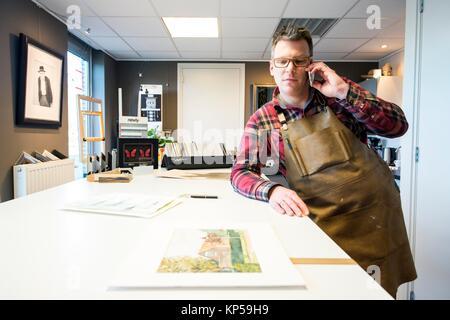 Goirle, Paesi Bassi. Metà maschio adulto artigiano e picture framemaker, parlando nel suo smartphone durante una Foto Stock