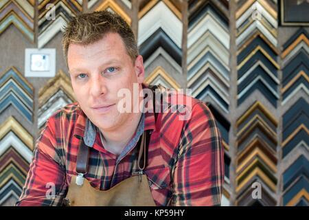 Goirle, Paesi Bassi. Metà maschio adulto artigiano e picture framemaker, ritratto dentro la sua officina di front Foto Stock
