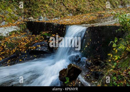 Una lunga esposizione di una piccola cascata in un torrente di montagna sul lato di Oyama, una montagna sacra vicino Foto Stock