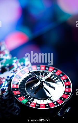 Tema del casinò. Alto contrasto immagine della roulette del casinò e poker chips su un sfondo bokeh di fondo. Posto per il testo.