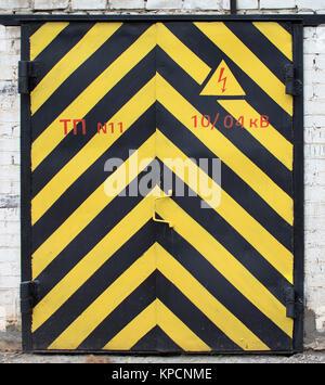 La vecchia porta di colore giallo e con una striscia nera Foto Stock