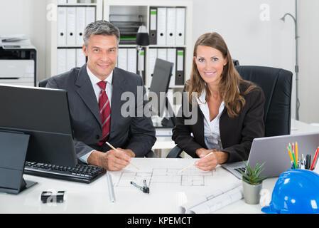 Gli architetti che lavorano sul progetto alla scrivania Foto Stock