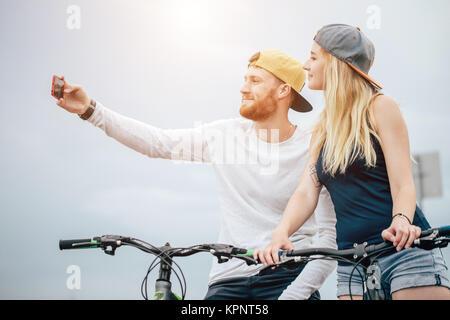 Coppia felice con la bicicletta prendendo selfie all'aperto Foto Stock
