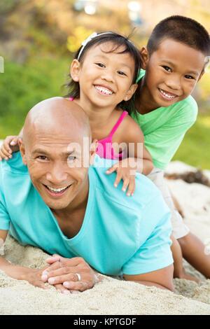 Padre a giocare con i suoi bambini sulla spiaggia. Foto Stock