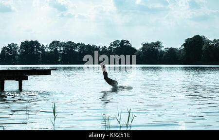 Donna che si tuffa nel lago durante le vacanze estive Foto Stock