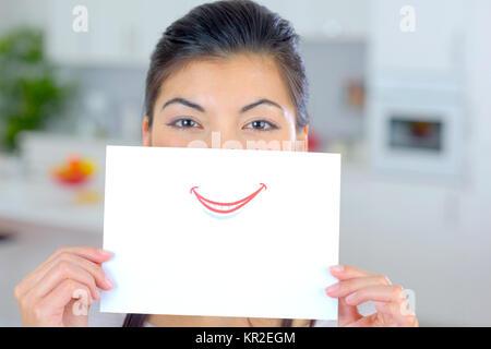 Donna che mantiene il foglio di carta sulla sua bocca Foto Stock