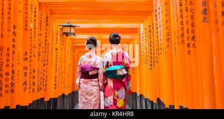 Due geishe fra il rosso in legno porta dei tori a Fushimi Inari Santuario a Kyoto, Giappone Foto Stock