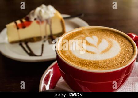 Caffè perfetto con cheesecake perfetta in background Foto Stock