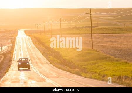 Automobile che viaggia sul lungo rettilineo di autostrada aperta al tramonto.